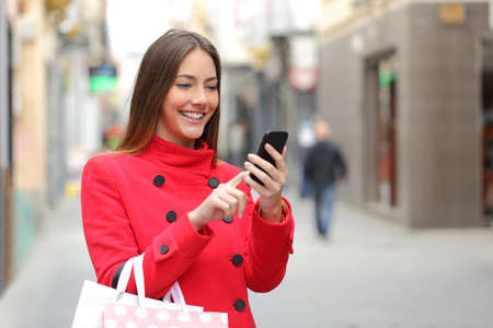 happy customer: Shopper woman buying online on the smart phone in the street Stock Photo