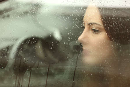 rainy: Sad woman or teenager girl looking through a steamy car window
