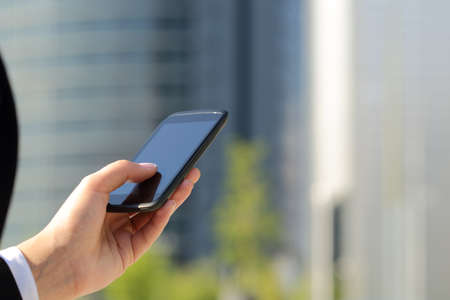 mobile sms: Business woman hand wearing suit texting on he smart phone with office buildings in the background in a sunny day Stock Photo
