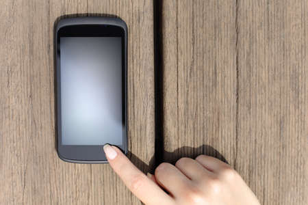 touch screen: Woman finger pressing a blank smart phone touch screen with wooden background Stock Photo