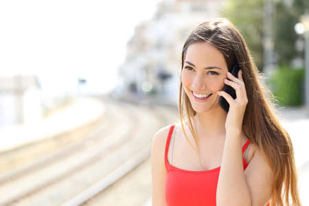 persona llamando: Señora que habla en el teléfono móvil mientras está esperando en una estación de tren en verano Foto de archivo