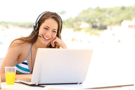 adolescentes estudiando: Muchacha que toma una videoconferencia en vacaciones de verano en una terraza snack bar en la playa Foto de archivo