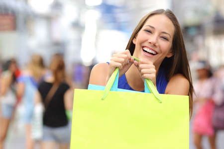 shopper: Shopper girl buying in a mall and holding a green shopping bag smiling to the camera
