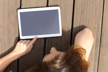 press media: Girl using and showing a blank tablet screen lying in a bench in a sunny day