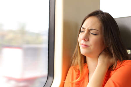 Stressed woman with neck ache sitting in a train wagon complaints Stockfoto