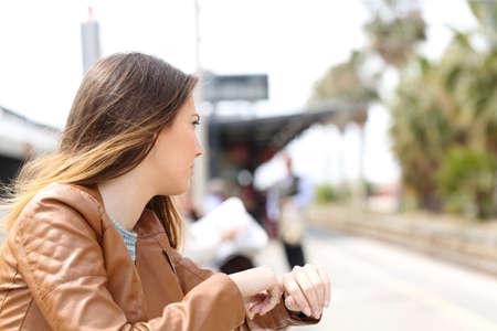 jovenes estudiantes: Muchacha enojada esperando en una estación de tren y mirando al ferrocarril