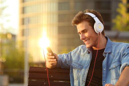 escuchando musica: Hombre feliz escuchar música desde un teléfono inteligente con un fondo de la ciudad calidez puesta de sol Foto de archivo