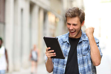 successful student: Euphoric winner man screaming with a tablet in the street