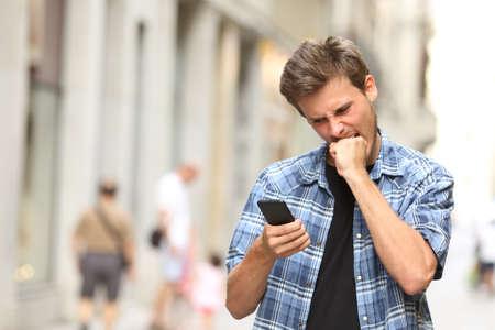 furioso hombre enojado viendo aplicaciones en el teléfono móvil en la calle Foto de archivo