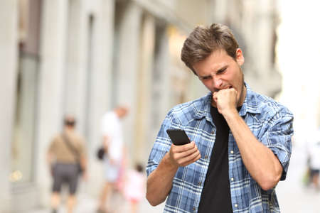bateria: furioso hombre enojado viendo aplicaciones en el teléfono móvil en la calle Foto de archivo