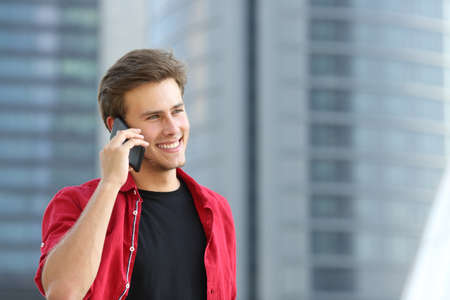 Entrepreneur business man talking on the phone with office buildings in the background Stock Photo