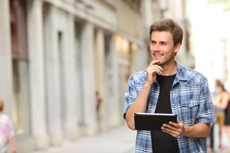 Happy man holding a tablet and thinking in the street