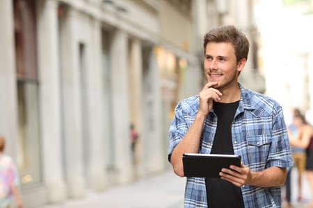 pensando: Homem feliz que prende um comprimido e pensando na rua