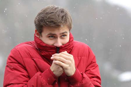 americana: El hombre temblando de frío invierno y frotándose las manos mientras está nevando