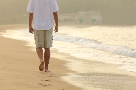 Back view of a man walking and leaving footprints on the sand of a beach at sunset