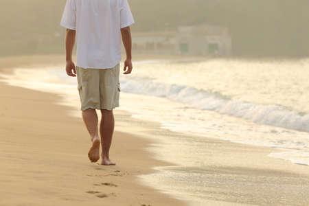 Vue arrière d'un homme qui marche et laissant des empreintes sur le sable d'une plage au coucher du soleil Banque d'images - 45076847
