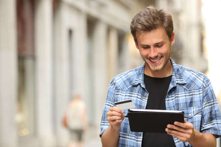 pagando: Hombre joven que compra en línea con tarjeta de crédito y una tableta en la calle