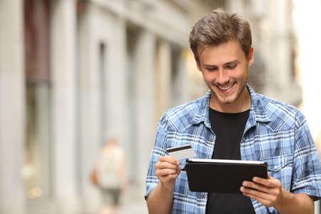 Jeune homme d'acheter en ligne avec une carte de crédit et une tablette dans la rue Banque d'images - 45076849