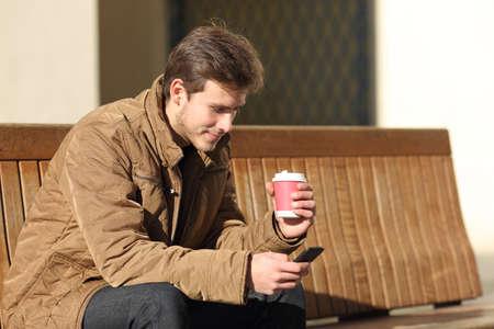 hombre tomando cafe: Hombre que usa un tel�fono elegante y con una taza de caf� sentado en un banco en la calle
