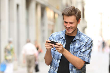 hand holding phone: Happy man playing game with a smart phone in the street