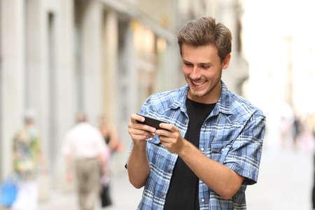 adolescente: Hombre feliz que juega al juego con un tel�fono inteligente en la calle