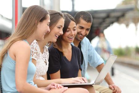 estudiantes: Cuatro amigos turistas felices que comparten un ordenador portátil sentado en una estación de tren mientras esperan