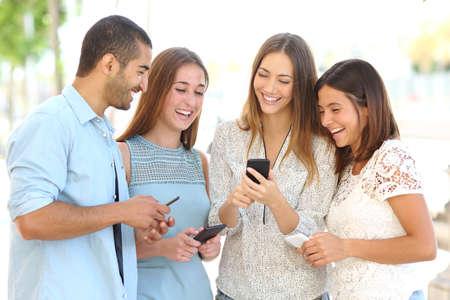 Vier vrienden lachen gelukkig en kijken naar sociale media in een slimme telefoon in de straat ieder met zijn eigen telefoon