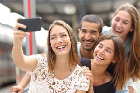 Groep van vier grappige vrienden nemen selfie met een slimme telefoon in een treinstation in de zomer