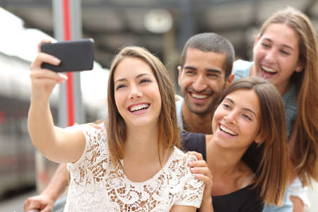 group of hands: Group of four funny friends taking selfie with a smart phone in a train station in summer Stock Photo