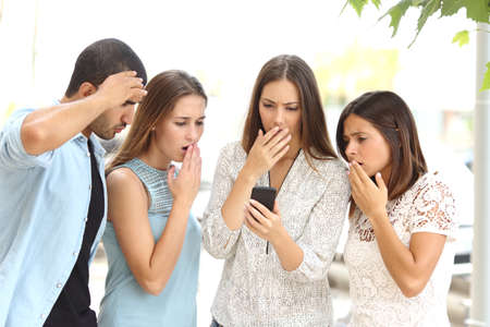 Four worried multi ethnic friends watching a smart phone in the street