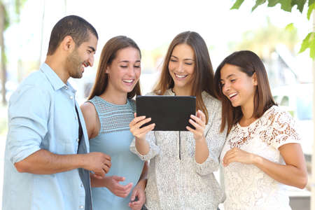 Front view of a group of four happy friends watching videos on a tablet in the street Stock Photo