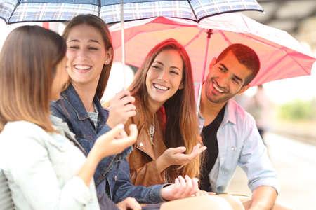 amistad: Cuatro amigos hablando al aire libre en un día de lluvia bajo los paraguas esperando en una estación de tren