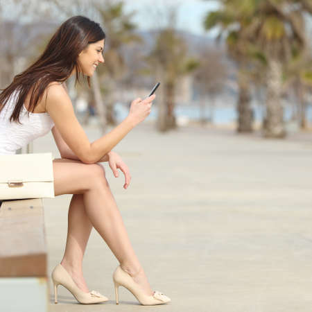 call girl: Side view of a fashion woman using a smartphone sitting on a bench in the street