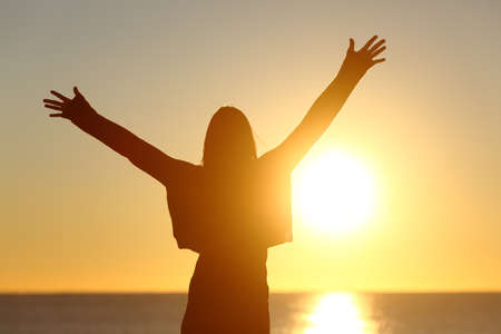 early morning: Free happy woman raising arms watching the sun in the background at sunrise