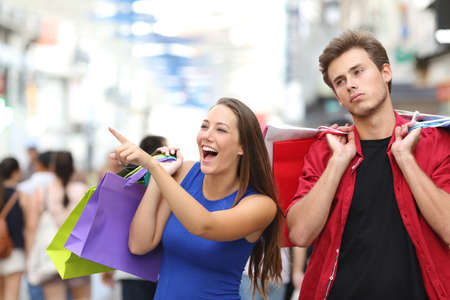 young man smiling: Bored man shopping with his girlfriend in a commercial street