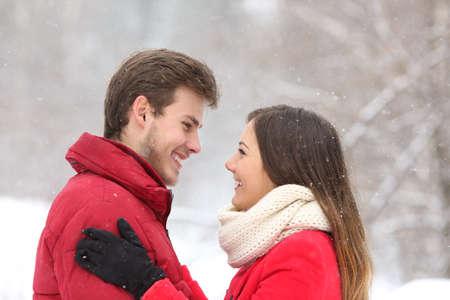 neige qui tombe: Couple regardant les uns les autres en hiver neige à la montagne