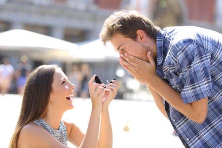 anillo de compromiso: Propuesta de una mujer pidiendo se casara con un hombre en el medio de una calle Foto de archivo