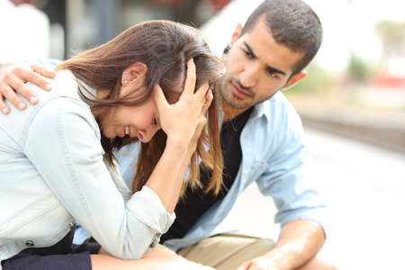 novios enojados: Vista lateral de un hombre musulm�n consolando una ni�a cauc�sica triste luto en una estaci�n de tren