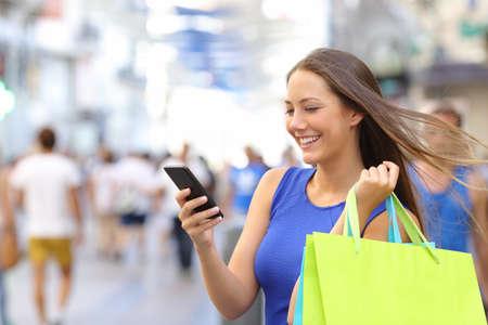 shopping: Mujer del comprador compras con un teléfono inteligente en una calle comercial