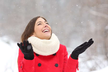 red snowflake background: Candid happy girl enjoying snow in winter wearing a red jacket
