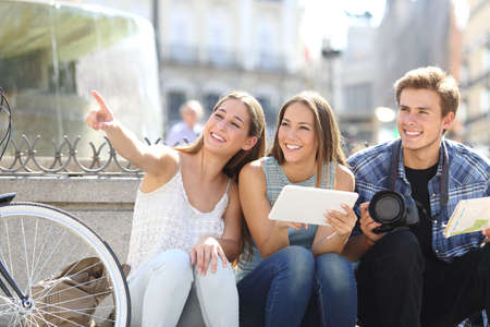 Tourist friends searching locations sightseeing in a city street Imagens - 47719262