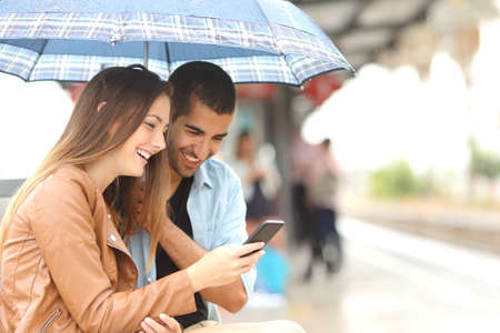 cellular telephone: Interracial couple sharing a phone in a train station while wait under an umbrella in a rainy day Stock Photo