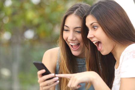 sorprendido: Amigos eufóricos ver vídeos en un teléfono inteligente y apuntando a la pantalla sorprendidos