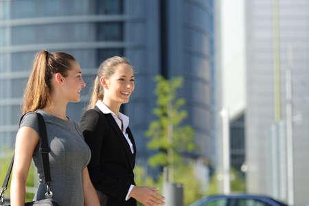 ウォーキングとバック グラウンドでオフィスビルの通りに話す 2 人の幸せなビジネスウーマン