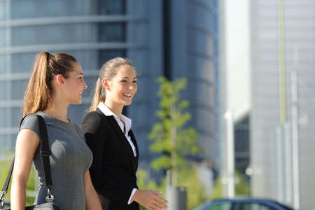 woman in office: Two happy businesswomen walking and talking in the street with office buildings in the background