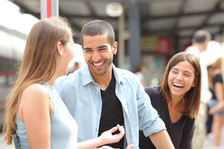 Three friends talking and laughing taking a conversation in a train station Stock Photo