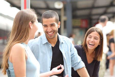 personas hablando: Tres amigos hablando y riendo teniendo una conversación en una estación de tren Foto de archivo