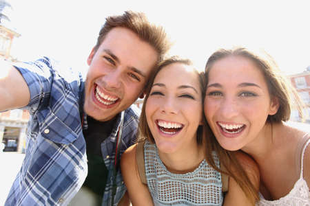trips: Group of happy teen friends laughing and taking a selfie in the street