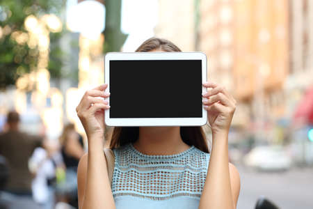 electronic tablet: Woman covering her face with a blank tablet screen showing display