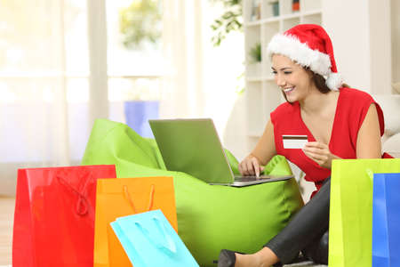 e shopping: Fashion woman buying online for christmas sitting on the floor with colorful shopping bags at home